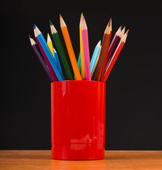 colour pencils in jar on wooden table