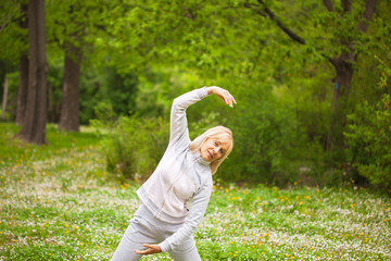 Adult woman in sport wear exercising in the park