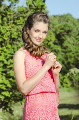 beautiful smiling woman wearing pink dress posing in green fores