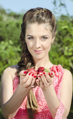 Beautiful young woman holding fresh tasty strawberries in hands