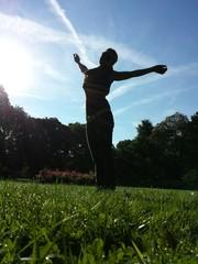 Junge Frau im Park Arme ausgestreckt