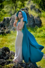 beautiful woman with blue cloak posing