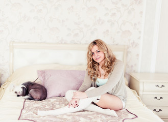 young woman and a dog sitting on a bed