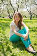 Beautiful  girl in green jeans sits on green grass.