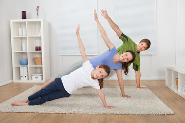 Fit Family Doing Side Plank Yoga At Home