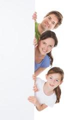 Happy Family Peeking From Blank Billboard