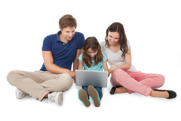 Family Sitting With Laptop Over White Background