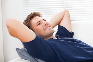 Man Lying On Sofa At Home