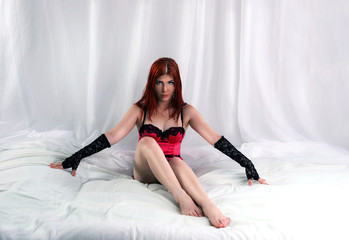 Young woman in sexy lingerie sitting in bed