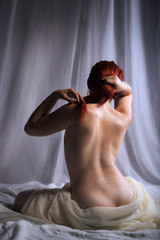 Rear view of a topless woman sittin in bed