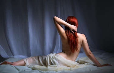 Back view of a naked redhead woman sitting in bed