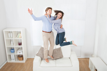 Playful Couple Jumping On Sofa