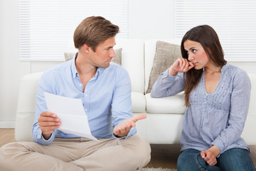 Couple Discussing Over Document At Home