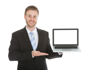 Confident Businessman Displaying Laptop Over White Background