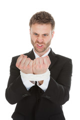 Frustrated Businessman Looking At Tied Hands