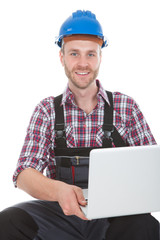 Manual Worker Using Laptop While Sitting On Trunk