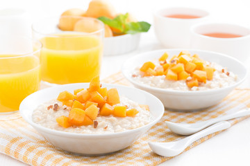 plates of oatmeal with fresh apricots, orange juice and tea