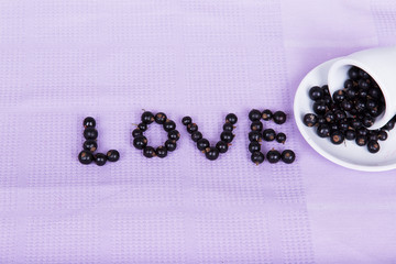"Inverted white cup with black currants with an inscription ""love"