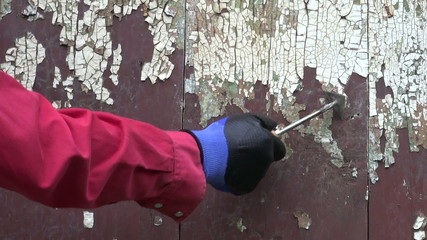worker hand scraping old paint from wooden wall