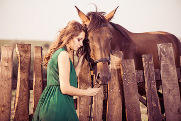 woman leaning to the horse at old wooden fence