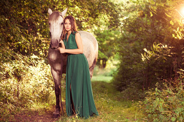 young woman with white horse at forest path