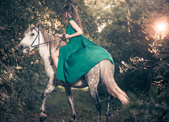 woman on horse at forest path