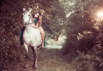 woman ride horse at forest path