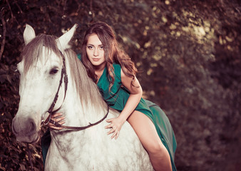woman on white horse at summer forest
