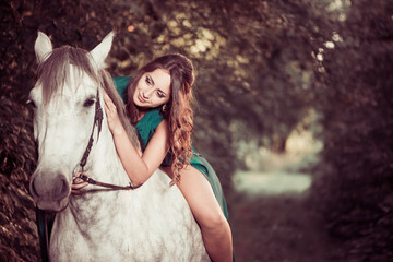 lovely young woman on a white horse at forest path