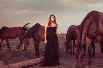 woman in black at grassland with brown horses