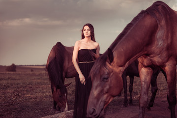young woman and brown horses at grassland sunset