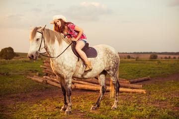 woman ride horse at summer sunset