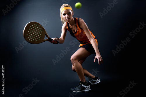 Beautiful woman playing padel indoor. Isolated on black. Poster