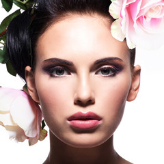 Closeup portrait of beautiful woman with pink flowers in hair