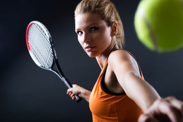 Portrait of beautiful woman playing tennis indoor.