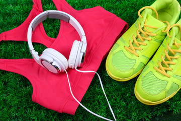 Sport clothes, shoes and headphones on green grass background