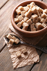 Brown sugar cubes in bowl on wooden background