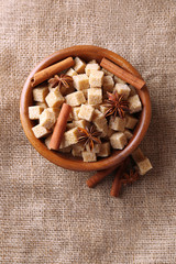 Brown sugar cubes and spices in bowl on sackcloth background