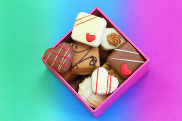 Assorted chocolates in box on colorful background