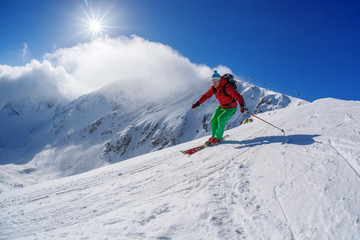 Skier skiing downhill in high mountains against sunset