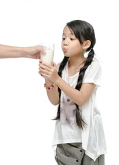 Mother giving her daughter a glass of milk