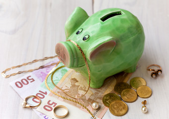 Green saving pig with money and jewelry