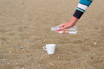 coffee cup on the sand and water bottle