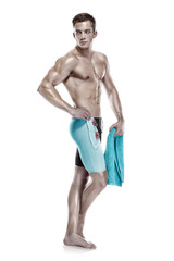 Young attractive caucasian man swimmer with goggles and towel