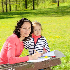 Mother & little daughter paint outdoors