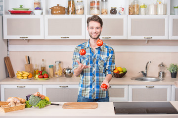 Cheerful young man juggling tomatoes while preparing food in