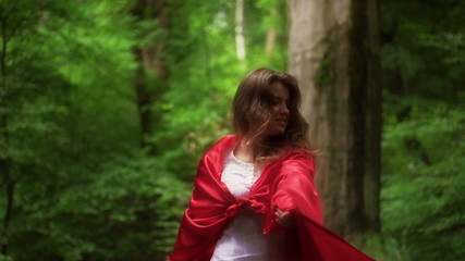 Woman in red cape turning round in forest, super slow motion