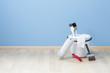 Leinwanddruck Bild - Farbeimer mit Pinseln und Eimer auf Parkett vor blauer Wand