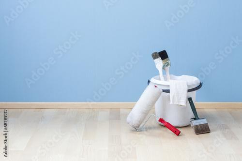 Leinwanddruck Bild Farbeimer mit Pinseln und Eimer auf Parkett vor blauer Wand