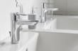 Leinwanddruck Bild - Wasserhahn mit Seifenspender auf weißem Keramikwaschbecken